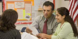 Teacher talking to parents at parent teacher conference
