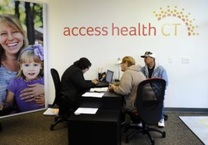 Gildred Ortiz, center and Julio Colon, right, receive help from outreach worker for Access Health CT, Cristela Solorio Ruiz during a grand opening for Connecticut's health insurance exchange's first insurance store, Thursday, Nov. 7, 2013, in New Britain, Conn.  The site, where people can visit to sign up for health coverage, is the first in the nation. (AP Photo/Jessica Hill)